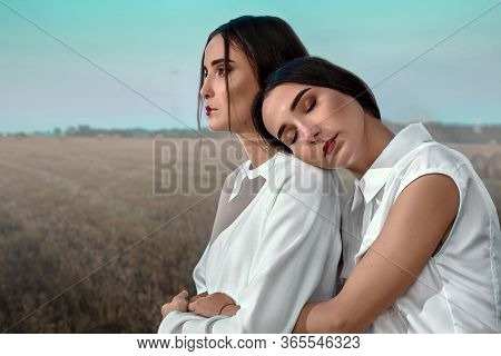 Portrait Of Two Dark-haired Sisters Girls In Stylish Clothes, Against The Background Of A Field And