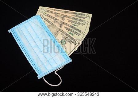 Medical Mask And Dollars Bills On A Black Background. Respiratory Protection Against Viruses. Epidem
