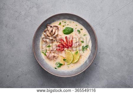 Tom Kha Gai Or Thai Coconut Chicken Soup In Matte Gray Bowl On Concrete Backdrop. Tom Kha Gai Is Tha