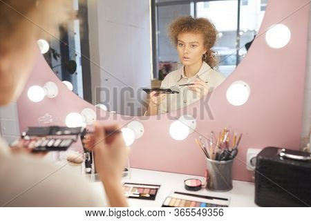 Reflection Portrait Of Young Curly-haired Woman Applying Make Up While Looking At Vanity Mirror In P