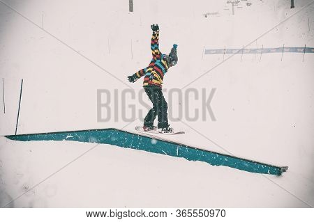 Freerider Snowboarder Doing Basic Snowboard Rails Trick In Freestyle Snowpark