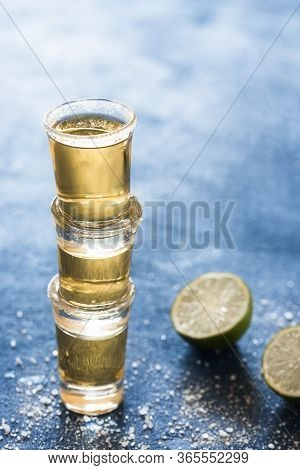 Three Shots Of Tequila Stacked, On A Blue Table. Gold Tequila Glass With Lime And Salt. Aromatic Str