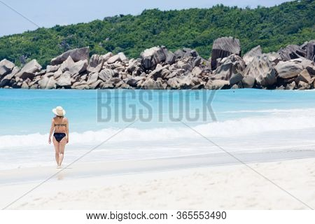 Tropical Beach, Turquoise Blue Water Surrounded With Huge Rocks, And A Walking Woman In Sun Hat.