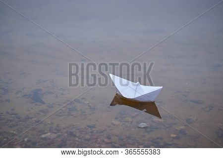 Origami Paper Boat Floating On The Surface Of Blue Water. Paper Origami.