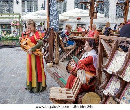 Tallinn Estonia 25 July 2018. On The Street Of The Old Town Of Tallinn Girl In A Ethnic Clothes Adju