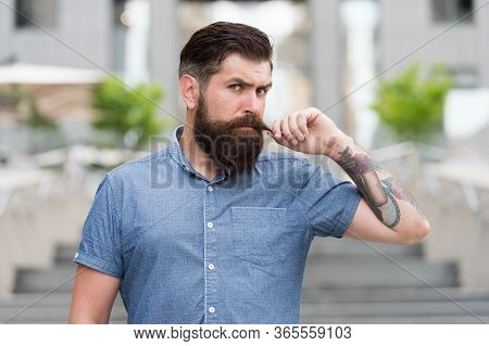 Obsessed About His Moustache. Bearded Man Twirl Moustache Urban Outdoor. Hipster Wear Long Beard And