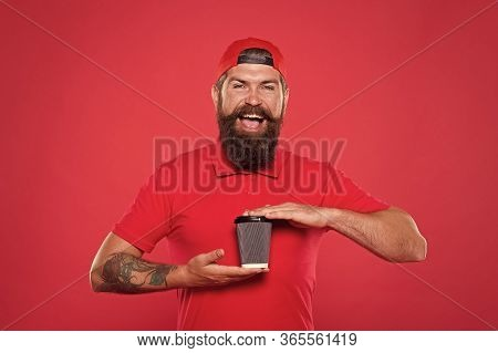 Bearded Man Drink Tea Red Background. Brutal Hipster In Uniform. Happy Barista Hold Coffee Cup. Take