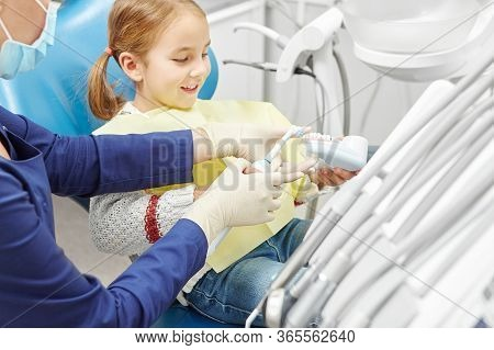 Dentist Educating A Little Girl About Proper Tooth-brushing, Demonstrating On A Model.
