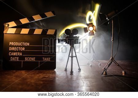 Movie Concept. Miniature Movie Set On Dark Toned Background With Fog And Empty Space. Silhouette Of