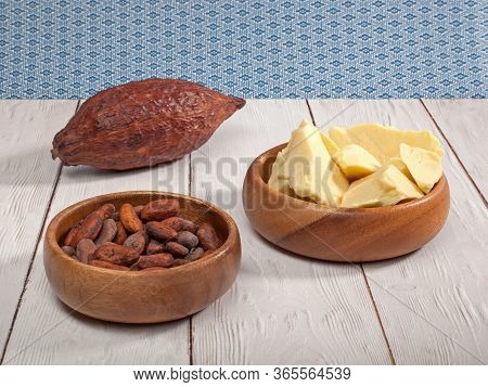 Pieces Of Natural Cocoa Butter In Bowl With Cocoa Beans And Cocoa Pod