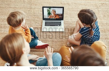 Family Children And Grandchildren   Enjoying Video Conversation Via Laptop With Grandmother While Si