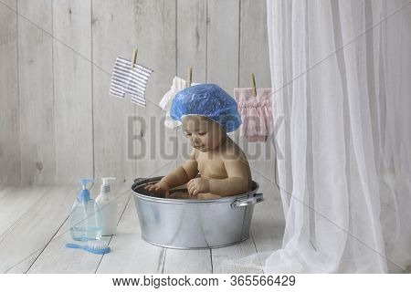 One Year Old Baby Girl Takes Bath. In Blue Swimming Cap. Bathroom. The Girl Bathes In A Basin. Cloth