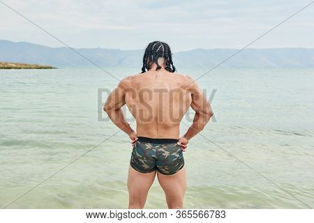 Young Man On The Beach, Young Muscular Man Exercising On The Beach, Young Muscular Man Doing Bodibui