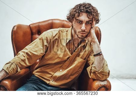 Portrait Of A Serious Young Adult Guy With Curly Hair, Wearing Luxury Orange Shirt While Sitting On