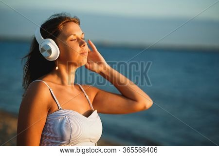 Woman With White Headphones Relaxing On River Shore And Listening Music On Sunset. Young Beautiful T