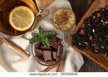 Fragrant Flower Tea With Lemon And Cinnamon, A Plate With Sweets: Chocolate, Honey And Mint, And Dry