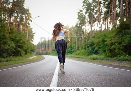 Beautiful Caucasian Young Girl Athlete Runs Sunny Summer Day On Asphalt Road In The Pine Forest View