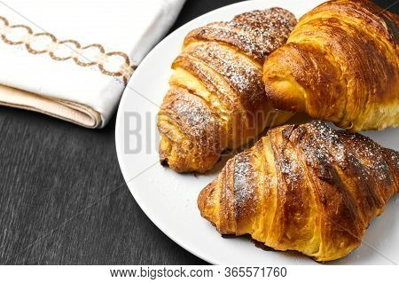 Freshly Baked Plain Croissants On A White Plate Near Serviette On A Black Wooden Background. Homemad