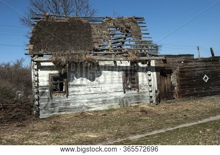 Old Dilapidated Wooden House With Whitewashed Walls And Thatched Leaky Roof Against The Sky. Behind