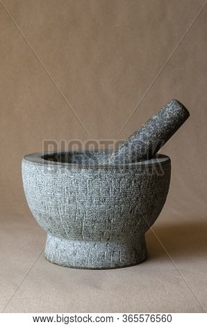 Gray Stone Mortar With Pestle. Close-up Of A Kitchen Granite Mortar On A Beige Background. Copy Spac