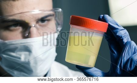 A Doctor Testing Urine Sample. Fresh Specimen In A Cup For Examining.