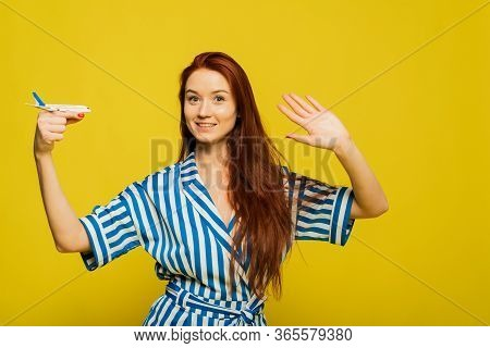 The Girl Flies Away On Vacation. Have A Nice Vacation, Bye Bye. Lovely Woman Holds A Model Airplane.