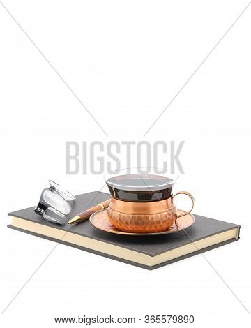 Hardcover Notebook Closed With A Cup Of Tea, Reading Glasses And A Pen On Top Of It Photographed On