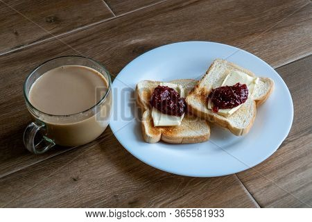 Cup Of Coffe With Milk And Two Slices Of Toasted Sandwich Bread With Butter And Raspberry. Breakfast