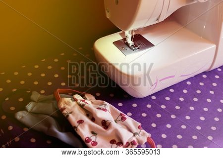 White Sewing Machine Resting On A Table Next To Homemade Chinstraps In Colorful Fabric. Homemade Mas