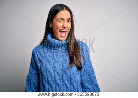 Young beautiful brunette woman wearing casual turtleneck sweater over white background winking looking at the camera with sexy expression, cheerful and happy face.