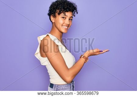 Young beautiful african american afro woman wearing casual t-shirt over purple background pointing aside with hands open palms showing copy space, presenting advertisement smiling excited happy