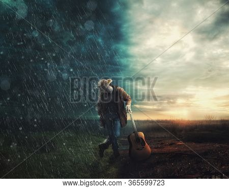 Cowboy With A Guitar Standing At A Line Between Rain And Sun . Line Between Happiness And Sadness .