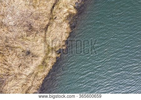 Dry Grass On River Shore And Water With Sky Reflection. Natural Patterns. Aerial Drone View