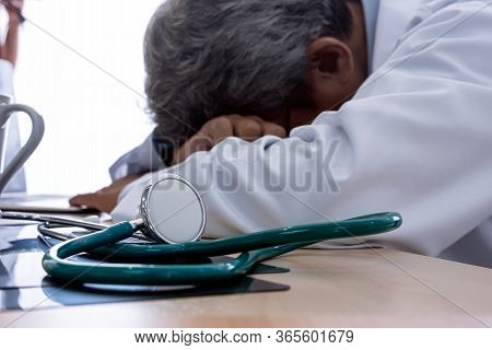 Senior Elderly Doctor Sleeping On His Deck At Medical Hospital Feel Tired Exhausted Form Overwork.