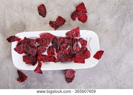 Diet Healthy Eating Concept. Dried Beet Chips Or Baked Beets In A White Rectangular Plate, On A Gray