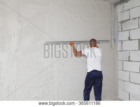 Kyiv, Ukraine - May, 12, 2020: A Handyman, Building Contractor Is Skim Coating, Finishing, Plasterin