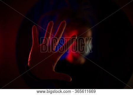Medical Worker In A Medical Mask In Defocused. Medic Girl In A Dark Room With A Red And Blue Light.