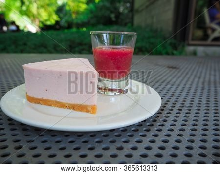 Slice Of Plain Cheesecake With Cranberry Sauce On White Plate Decorated
