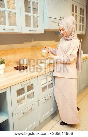 Beautiful Muslim Woman In Hijab Cooks Supper And Pours Pasta Into Saucepan Standing On Electric Stov