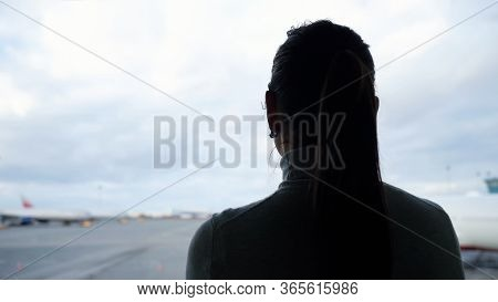 Woman Silhouette With Ponytail Looks At Airplanes On Airfield Apron From Airport Terminal Close Back