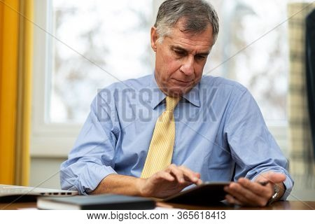 Serious senior businessman reading business documents in office. Senior manager reviewing quotation of company for contract. Portrait of executive senior planning new business project sitting at desk.