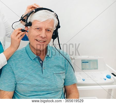 Impedance Audiometry, Diagnosis Of Hearing Impairment. An Elderly Man Getting An Auditory Test In A