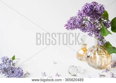 Purple Lilac Blossom Standing In A Small Perfume Bottle On White Background