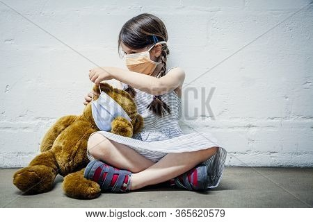 Young Girl Wearing A Mask Placing A Mask On Her Teddy Bear During Covid-19 Pandemic.