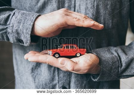 Male Hands Holding And Protecting A Red Toy Car. Conceptual Image Of Insurance And Road Safety.