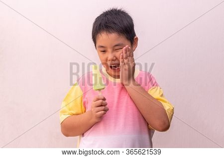 Asian Boy With Hypersensitive Teeth Eating Eating A Colorful Frozen Popsicle In The Summer