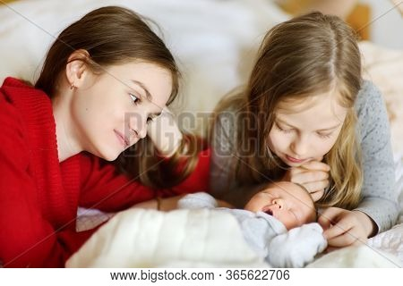 Two Big Sisters Admiring Their Sleeping Newborn Brother. Two Young Girls Holding Their New Baby Boy.