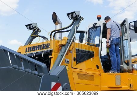 Moscow, Russia - June 4th 2016: Two Men Inspecting Operator Cabin Of 50 Tonn Liebherr Bulldozer, Goi