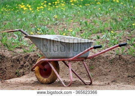 Metal Wheelbarrow With Shovel Near The Heap Of Soil And Meadow With Green Grass And Blooming Dandeli