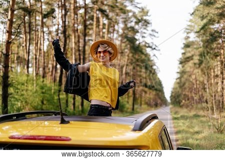 Smiling Woman Standing Out Of Yellow Car Sunroof. Happy Girl In Leather Jacket And Sunglasses Smile.